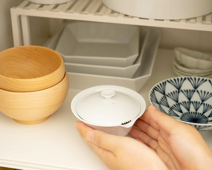 A woman stores the Houhin teapot in the cupboard