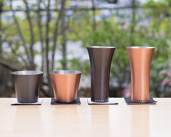 4 different copper tumblers and copper drinking cups on the table