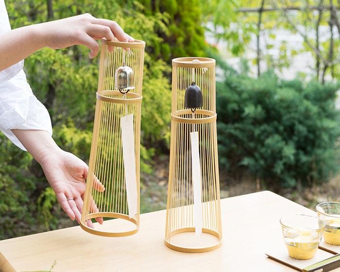 テーブルに置かれた2種類のWDH置き風鈴を女性が1つ手に持っている様子