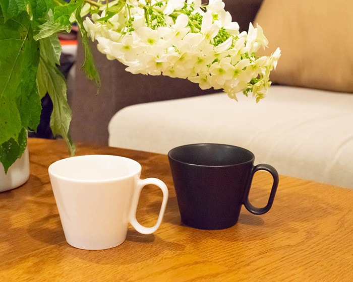 Plain white and black coffee mugs on the table