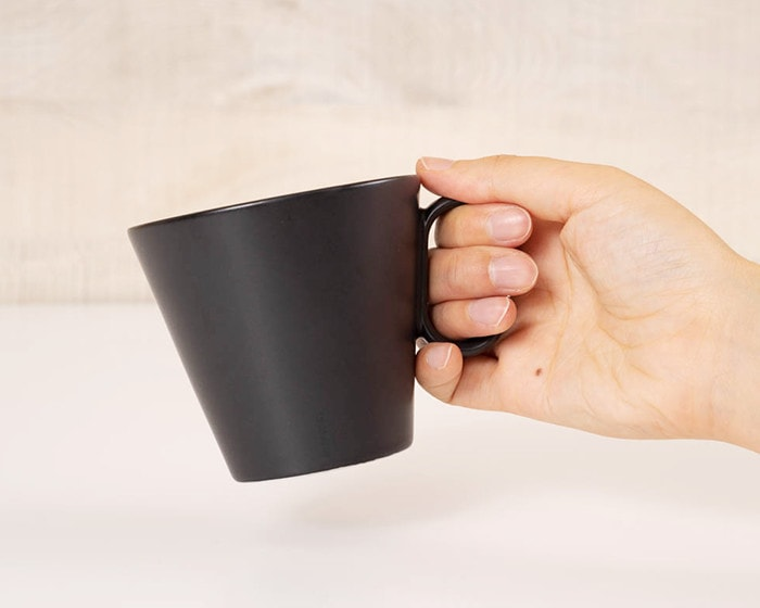 A woman has black coffee mug