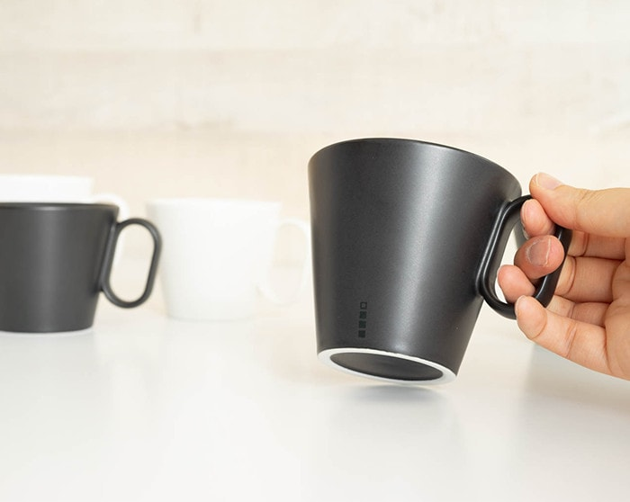 A woman has large black mat coffee mug