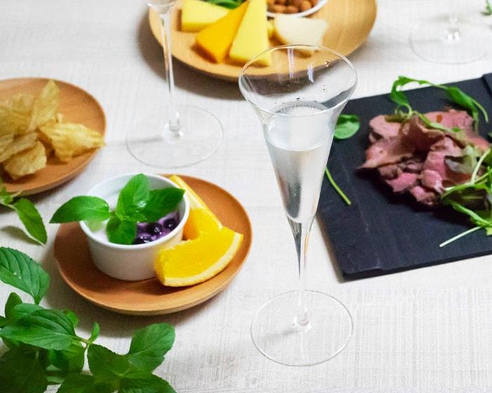 日本酒の入ったSAKEグラスと周りにはフルーツやお肉などの食事が並んでいる