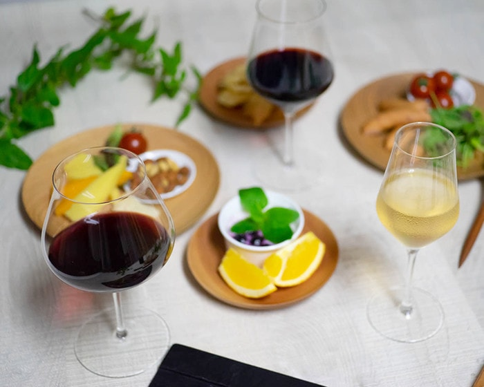 Wine glasses filled with wine and wooden plates with fruits and salad