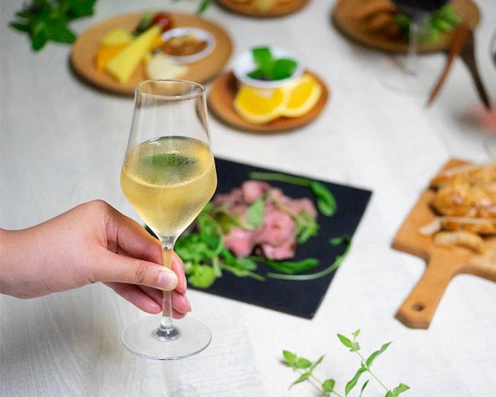 女性が白ワインが注がれたワイヤードビーンズのワイングラスを持っている