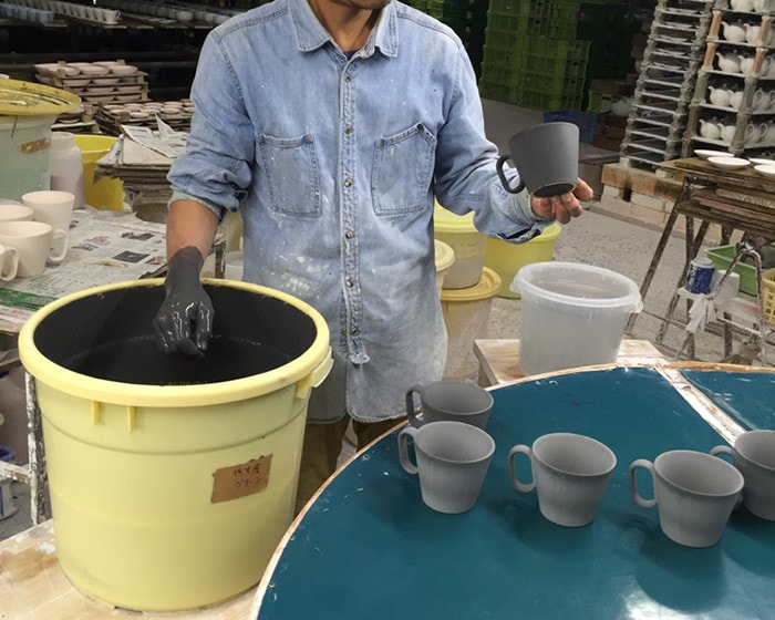Craftsman of Tsujiyo Ceramics Factory glazes mugs