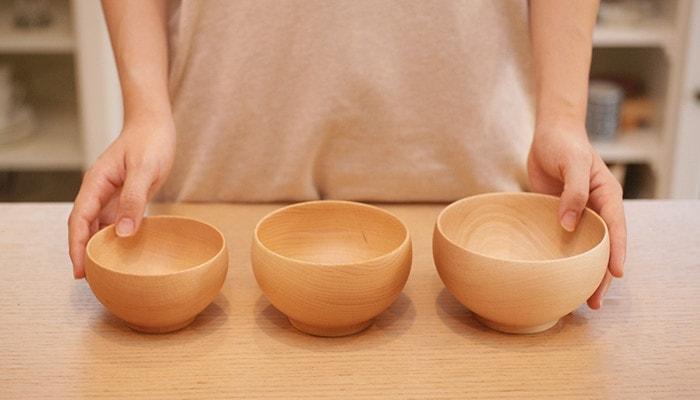 テーブルにめいぼく椀の小中大が並んでいて女性が手を添えている