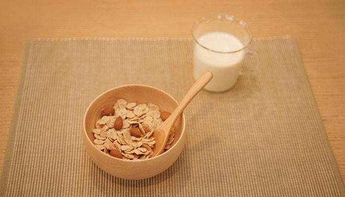 めいぼく椀にコーンフレークとナッツがはいっていて、奥には牛乳の入ったカップが置いてある