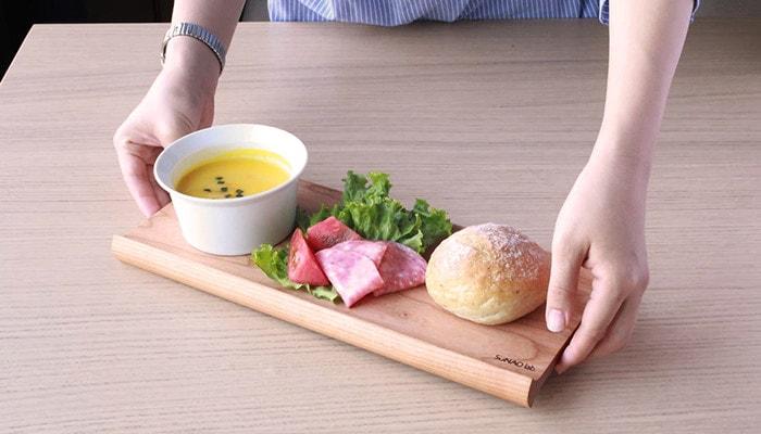 スナオラボのカフェトレーにサラダやパン、カップに入ったスープが乗っていて女性がトレーを持っている様子
