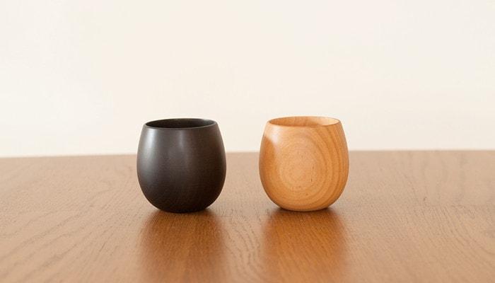 テーブルの上に我戸幹男商店のSAKURAたまごの木製カップが2つ並んでいる