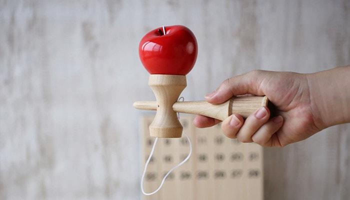 モアツリーズデザインのりんごのけん玉を手に持っている様子