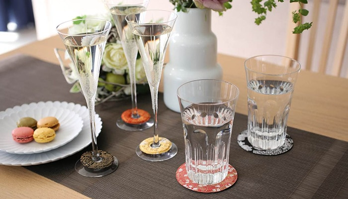 テーブルにお菓子の乗ったお皿やグラスが置かれていてセメントプロデュースデザインのグラスマーカーやコースターを使用している