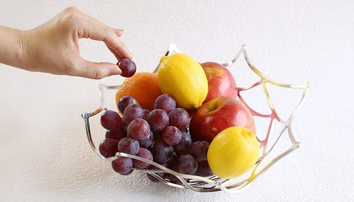 能作KAGOにフルーツが盛られていて横から女性がブドウのひと粒を持っている様子