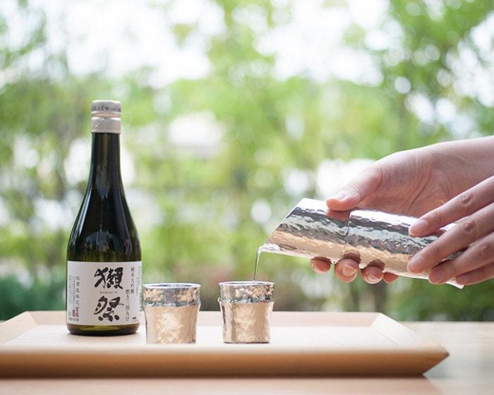 女性が能作の竹型酒器でお酒を注いでいる様子
