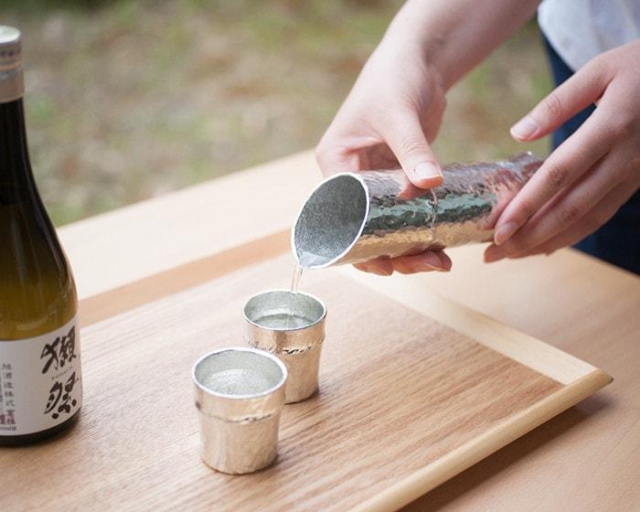 女性が能作の竹型酒器でお酒をぐい呑みに注いでいる