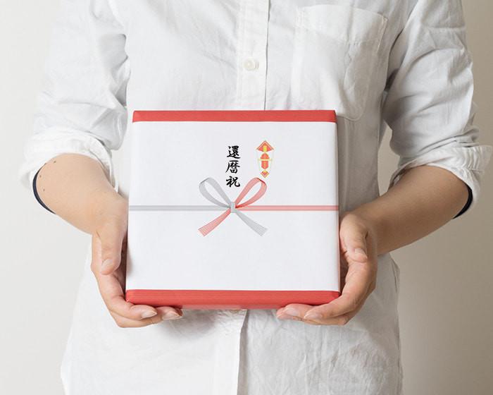 女性が還暦祝いの熨斗紙を掛けたプレゼントを手に持っている