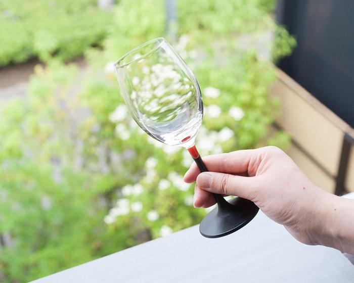 女性が鳥羽漆芸のうるしのワイングラス赤を手に持っている