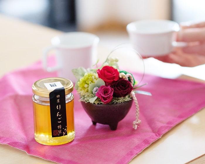 女性がお茶の入ったマグカップを持っている様子。テーブルにはプリザーブドフラワーやドライフラワーが置いてある