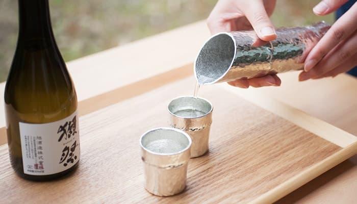 竹型の酒器セットでお酒を注いでいる様子