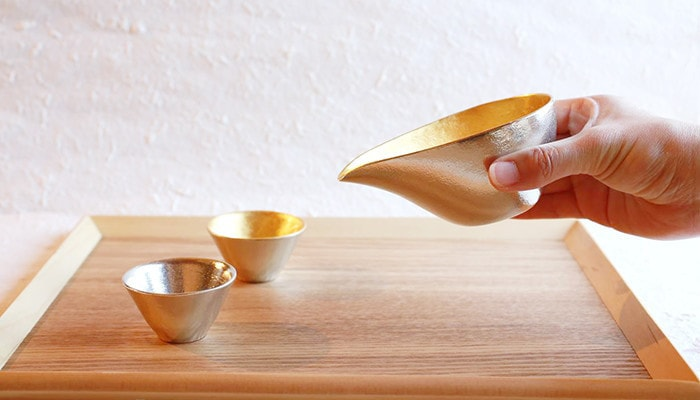 A woman has Katakuchi, and 2 Guinomi sake cups on the serving tray
