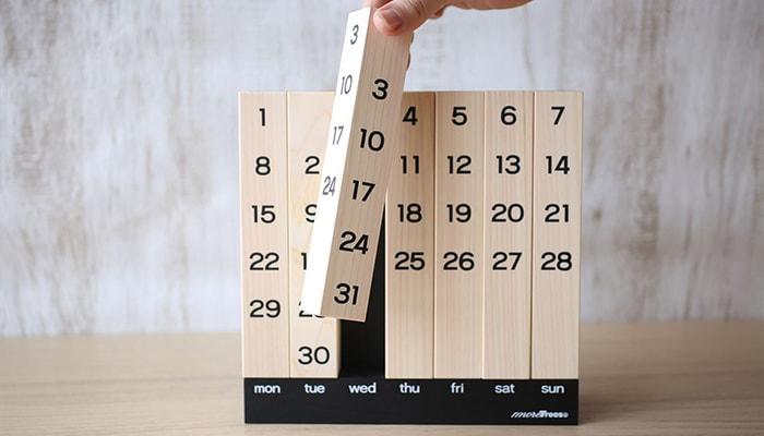万年カレンダーの角柱を一つ手に持っている