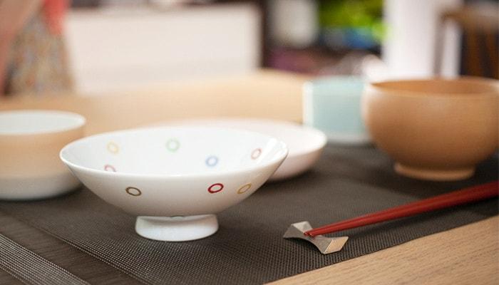 手前に平茶碗のカラフルドットとその他の食器がテーブルにセットされている