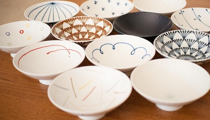 さまざまな柄の平茶碗が12枚並んでいる写真