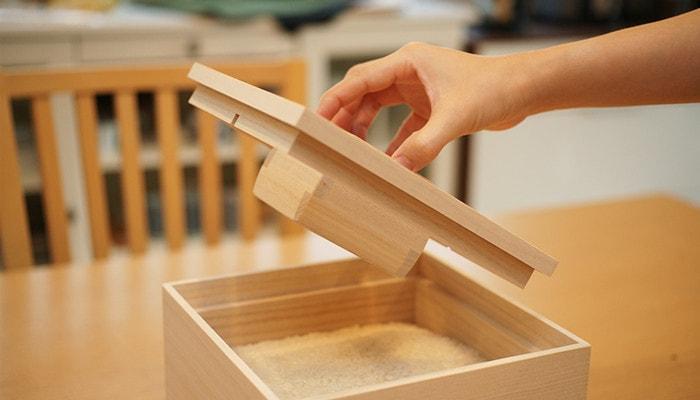 増田桐箱店の米びつの蓋を持っている様子