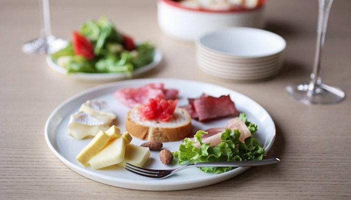 ラウンドプレートの上にサラダやチーズ、ブルスケッタが盛り付けられているワンプレート