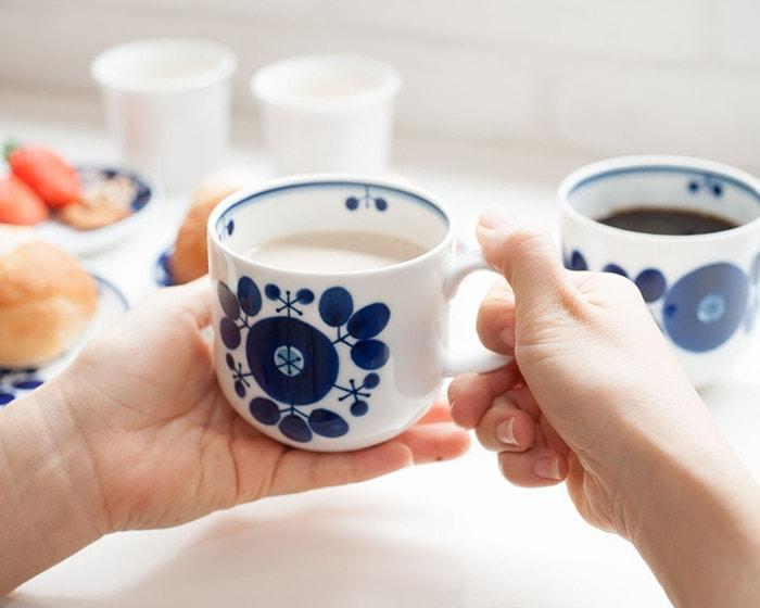 カフェオレの入った白山陶器ブルームのカップをもっている