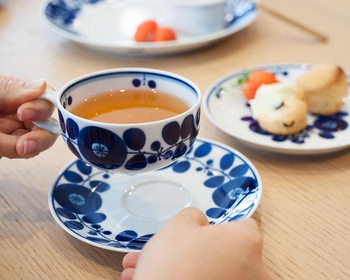 紅茶の入った白山陶器ブルームのティーカップを女性が手に持っている