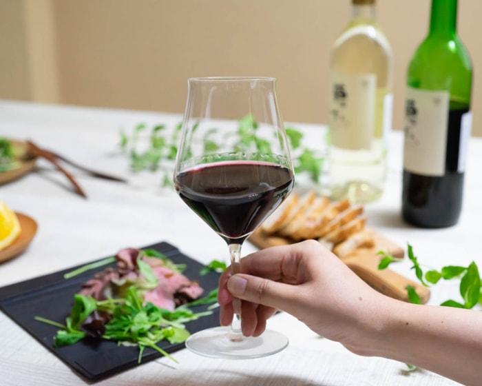 生涯を添い遂げるグラスと背景にはお肉やバケットなどワインに合う料理