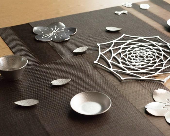 能作錫のさくら箸置きや小皿、KAGOなどがテーブルに並んでいる