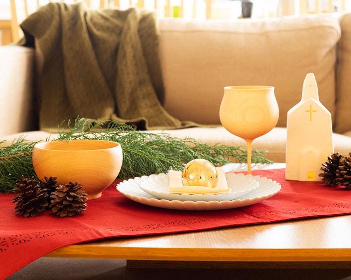 テーブルに赤いテーブルクロスや松ぼっくり、おしゃれな食器が並んでいる