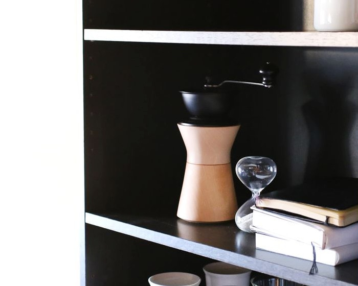 Stylish manual coffee grinder from MokuNeji on a bookshelf