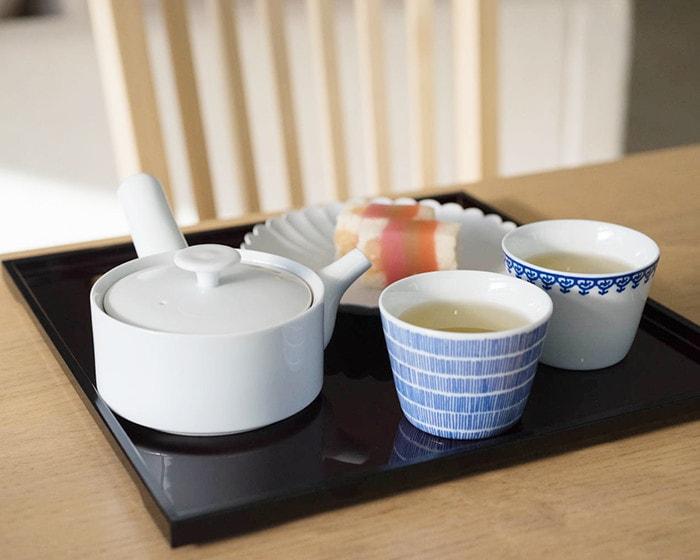 お盆の上にお茶の入ったそば猪口や和菓子、急須が並んでいる