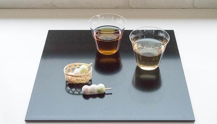 折敷の上にお茶の入ったコップと和菓子が乗っている