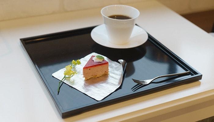 お盆の上にケーキの乗ったすずがみとコーヒーの入ったカップが乗っている