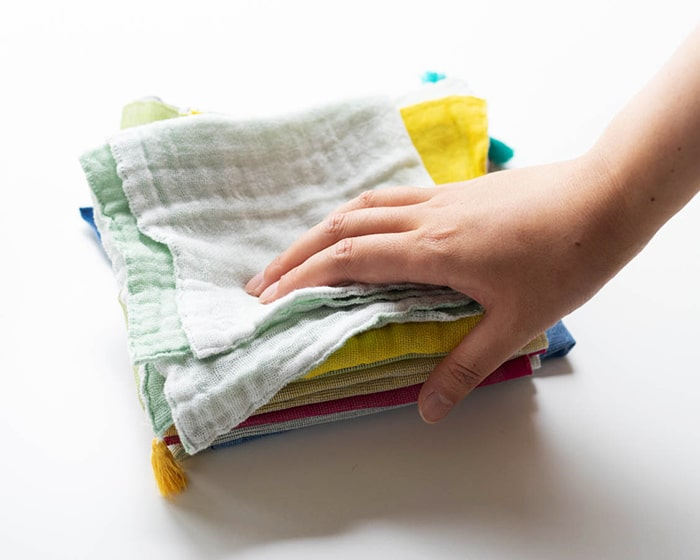 数枚重ねた蚊帳ふきんに手を添えている