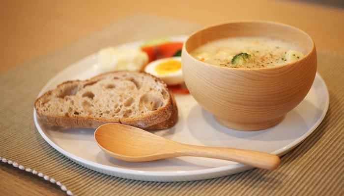 パンやおかずがのったラウンドプレートの上にスープの入っためいぼく椀とレンゲが乗っているワンプレート