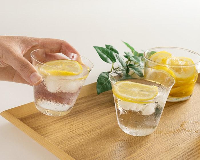 炭酸水とレモンの入った木村硝子店の薄玻璃(うすはり)ガラス・ベッロを女性が手に持っている