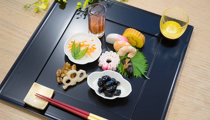 Special dinner with lacquer sake cup, gold chopsticks and chopstick rest on a tray