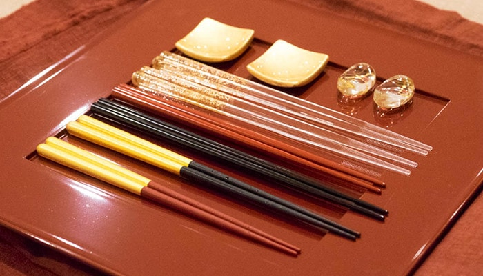 Some pairs of gold chopsticks and chopstick rests