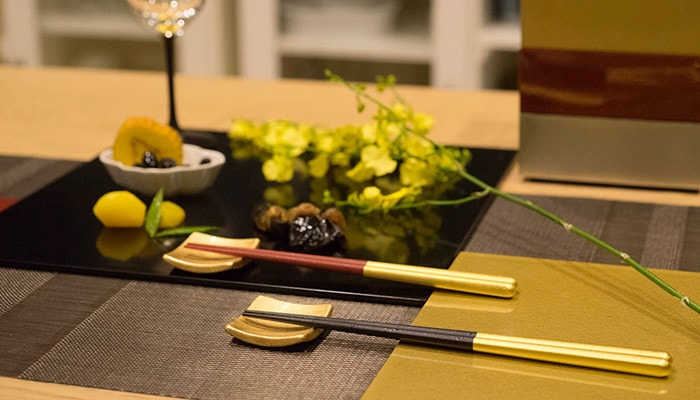 Gold chopsticks and chopstick rests on platters of the table
