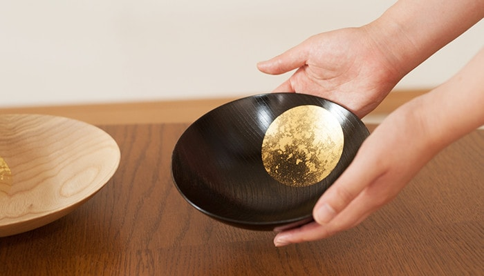 A woman has black Oborozuki bowl