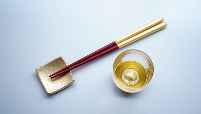 Set of gold chopsticks and lacquer sake cup