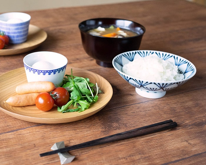 Flat rice bowls with rice and dishes on wooden plate