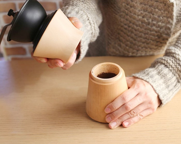 A woman opens the manual coffee grinder of MokuNeji