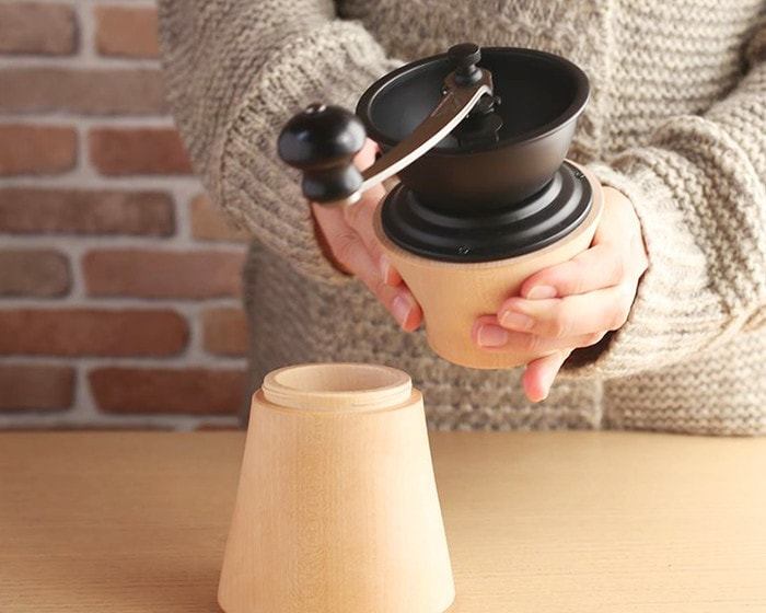 A woman is caring Coffee grinder