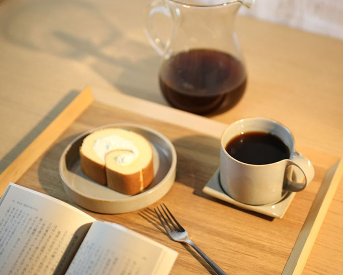Reading a book with a cup of coffee and a piece of swiss roll on Moderato series tableware